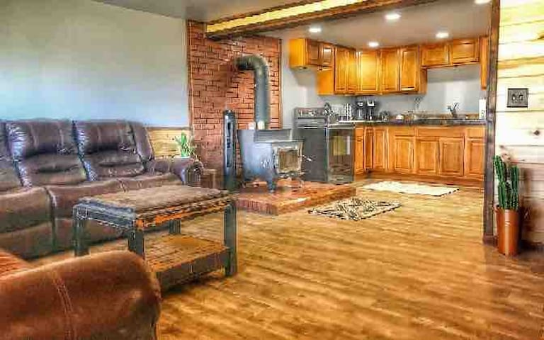 Spacious loft-style living room with two full size couches & smart TV extends to open kitchen