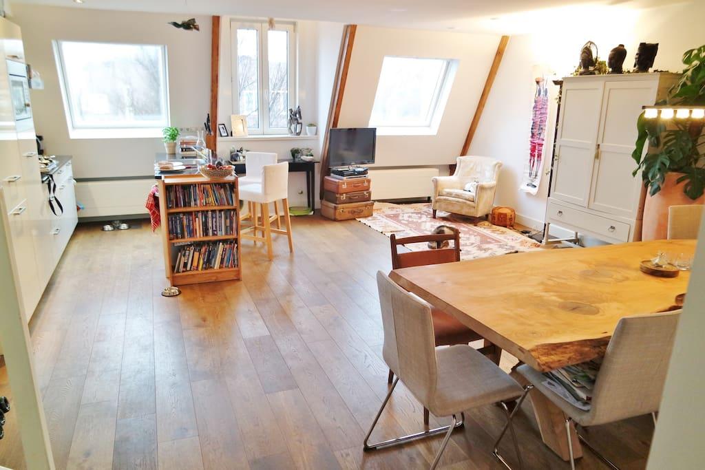 fourth floor with open kitchen, big dinner table, tv corner.