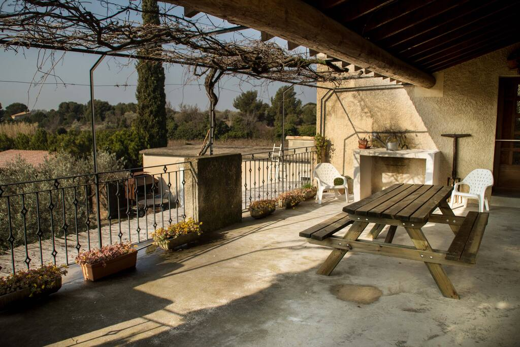 Grande terrasse fermée par un portillon, ombragée et équipée avec plancha.