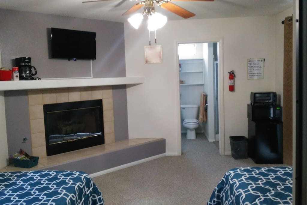 Bedroom with TV, Fireplace, fridge, coffee maker, & toaster.