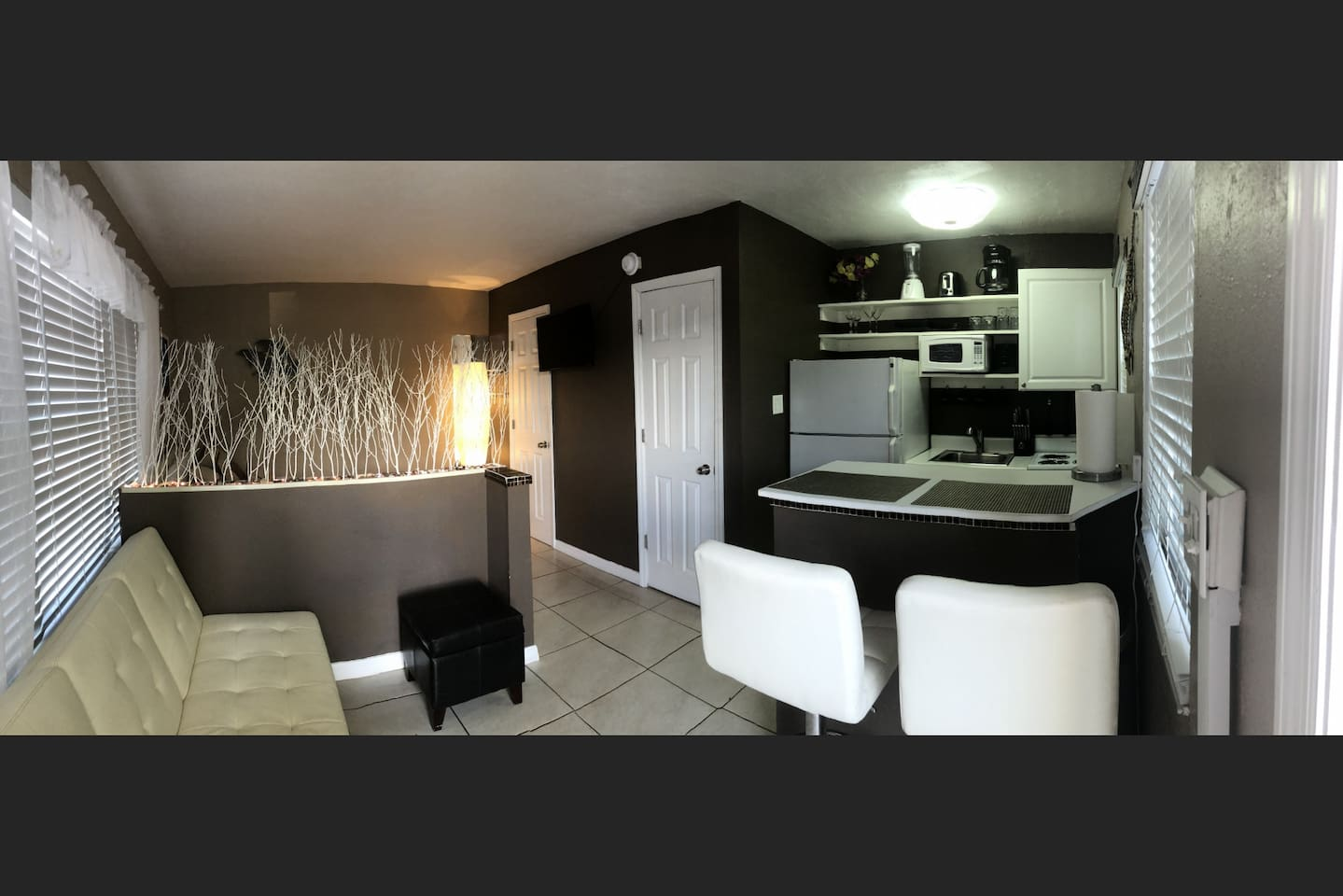 Unit 2 features an open design with a half wall separating the living and sleeping areas.  The half wall has a pleasant LED glow which can be dimmed.  The TV is centrally located and can be adjusted for multiple viewing angles