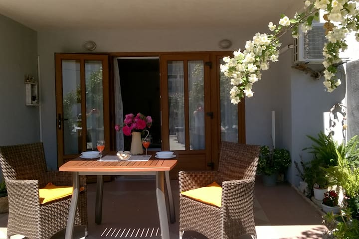 A sunny and pleasant terrace surroanded by a garden