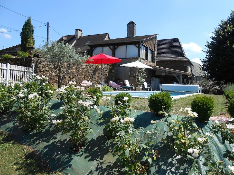 Piscine dominant la vallée de la Dordogne, avec le pool house derrière le volet.