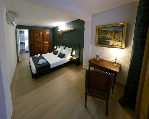 La chambre est climatisée. Au fond, la porte qui donne sur la chambre aux lits superposés.