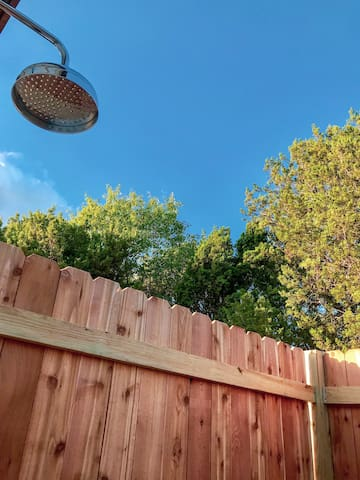Enjoy the private outdoor shower surrounded by trees, blue skies, and the sounds of birds.