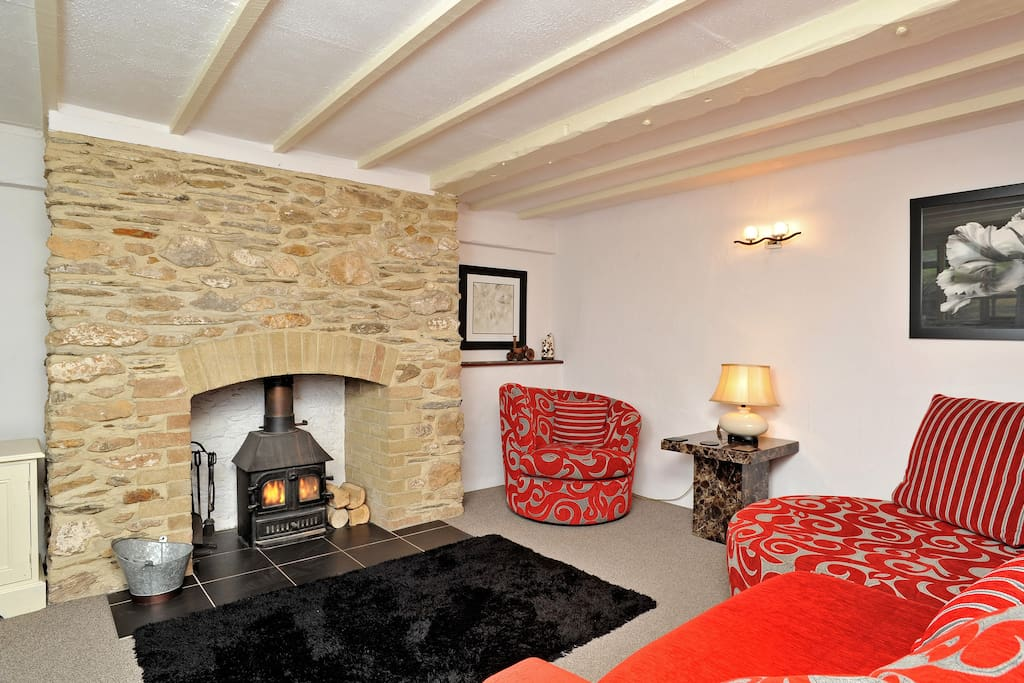Lounge room with large comfy sofa, tv DVD player and log burner.