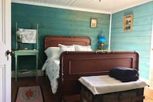 Rooms are furnished with local antiques. This one has a double bed and a window that looks out to the ocean and a boat marina