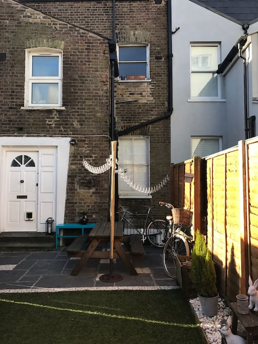Our outdoor patio area has a bench to fit 4-6 people and twinkly lights when it gets dark. Entrance to the house is via the garden gate and then front door in the garden
