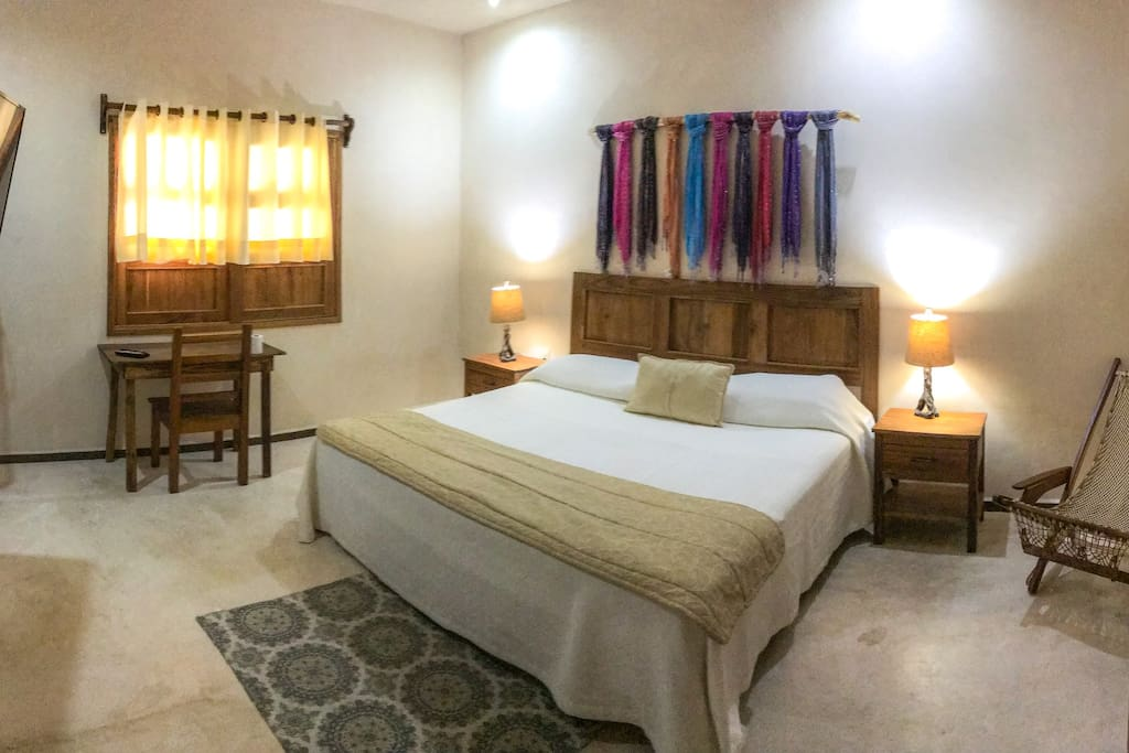 Bedroom with King Size bed, pillows, night lamps, MiniSplit A/C, Satellite TV, desk and a full private bathroom.