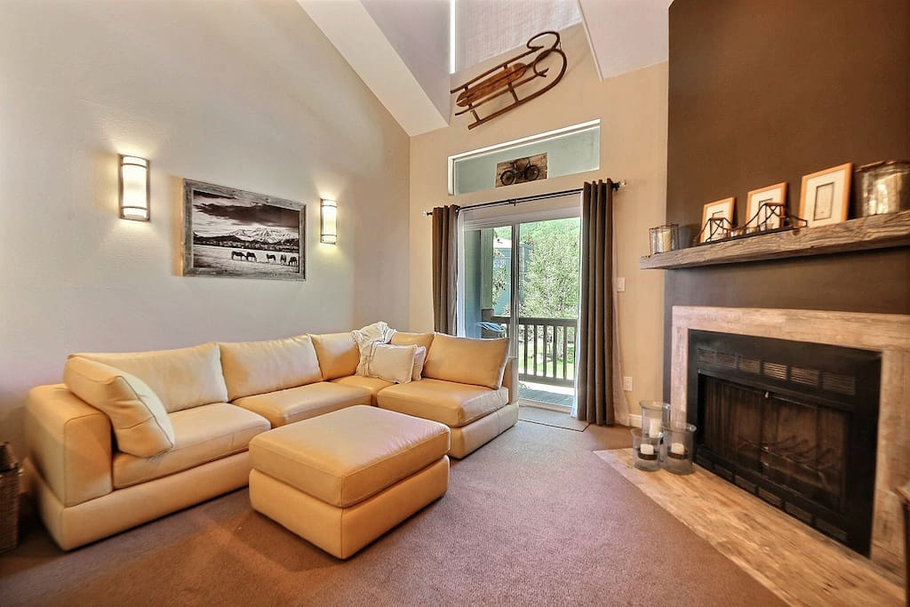Living room features an amazingly comply leather sectional. plasma TV,  and fireplace