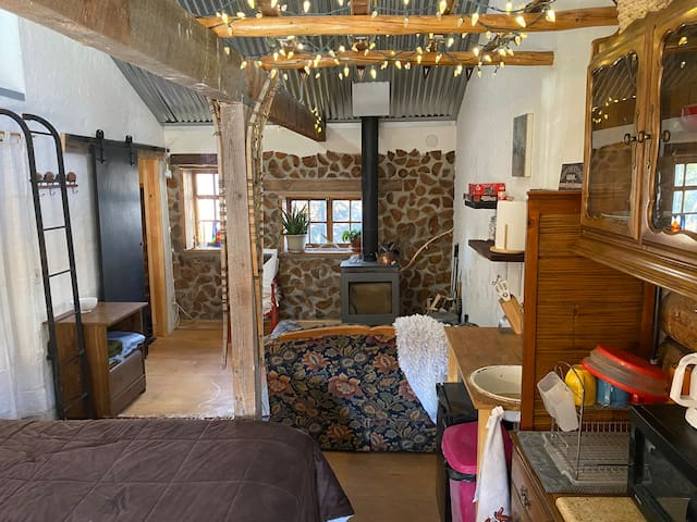 This is the Redtail Retreat Studio!  Real cordwood wall, a swedish wood-burning stove and loveseat.  There is also a propane heater that is thermostat controlled.