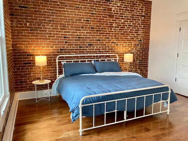 Main bedroom with king sized bed, exposed brick, a custom closet, wall-mounted TV, and adjoining bathroom.