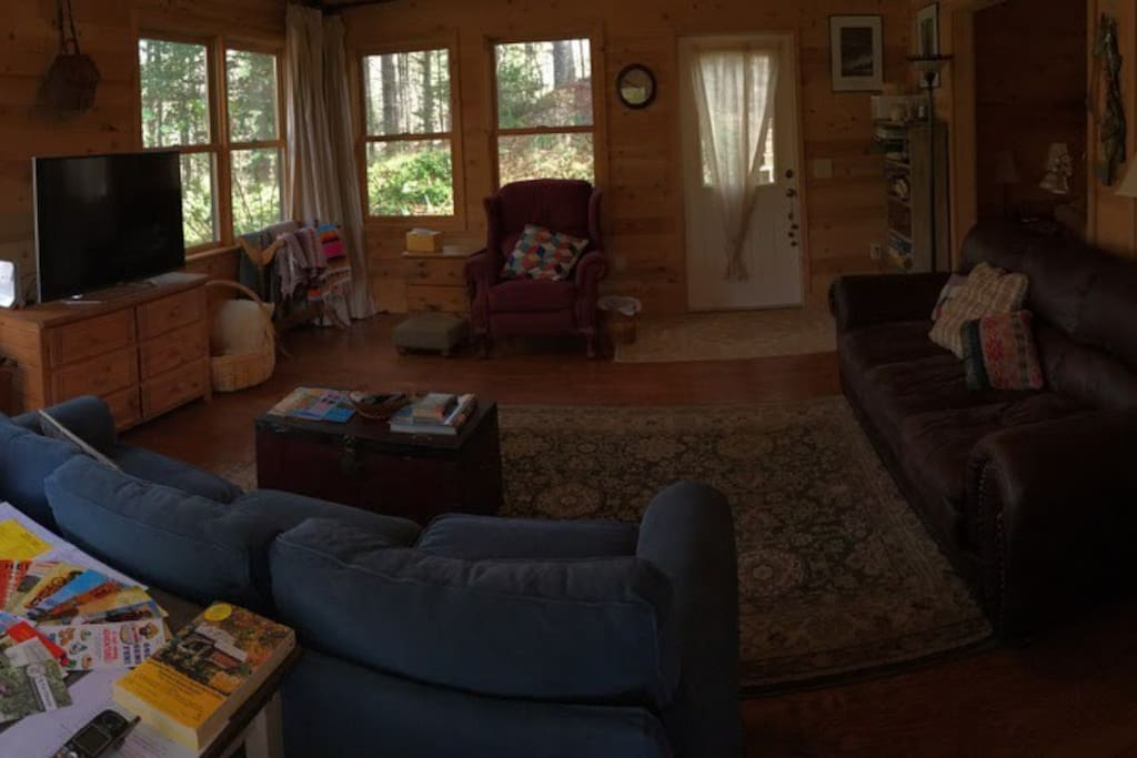This living room has witnessed many a family gathering. It features a sofa sleeper, two comfy chairs, a leather sofa, and tv with Sling, Roku, and blu-ray player. Board games, cards, toys, and a set of poker chips are on the shelves. Lincoln logs are in a drawer under the TV.