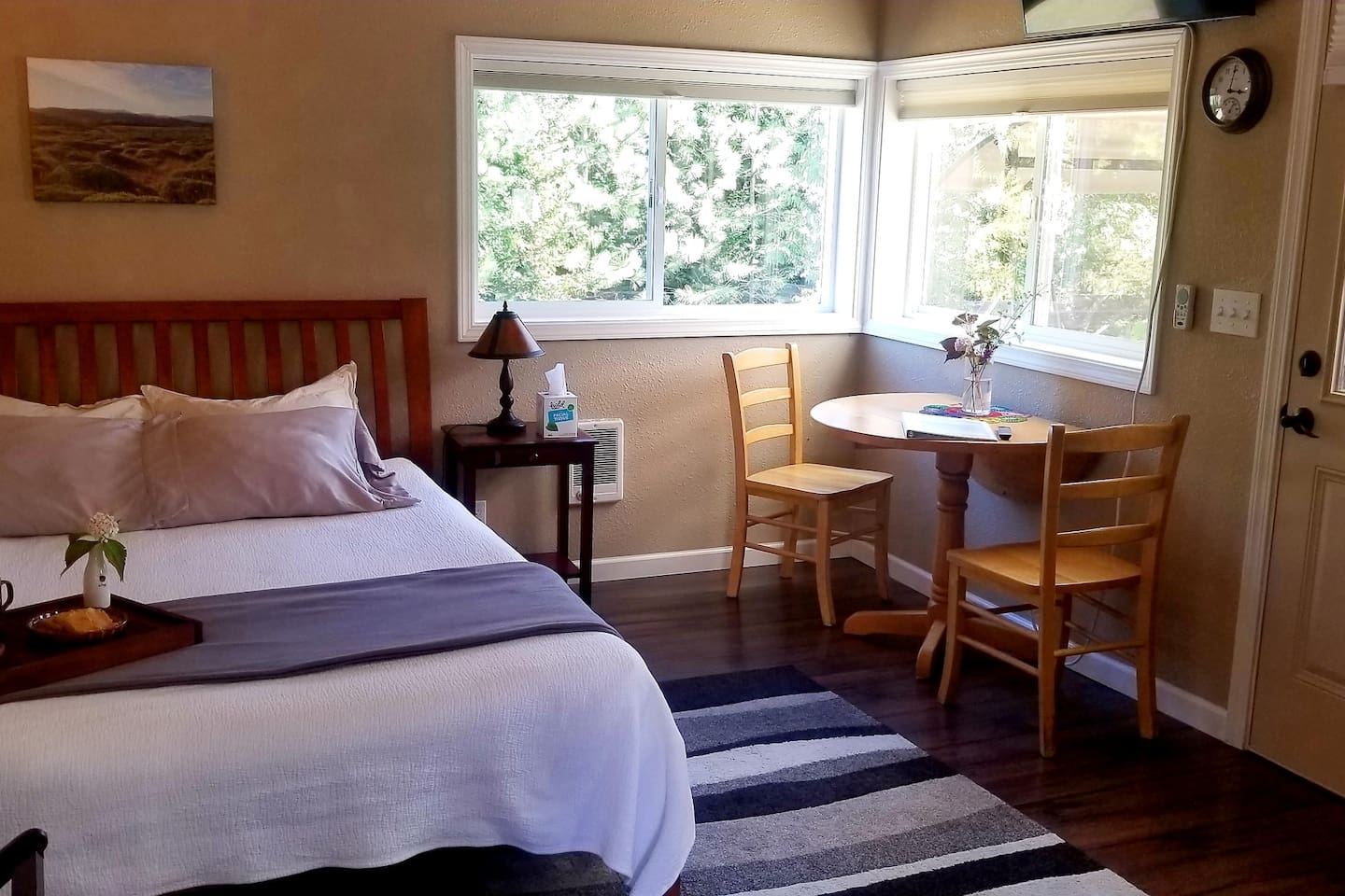 Cozy and comfortable accommodations. The television is mounted on the wall above the table and in view of the bed.