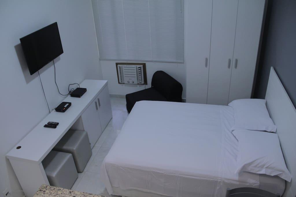 Cama, armário, poltrona cama e pufes.