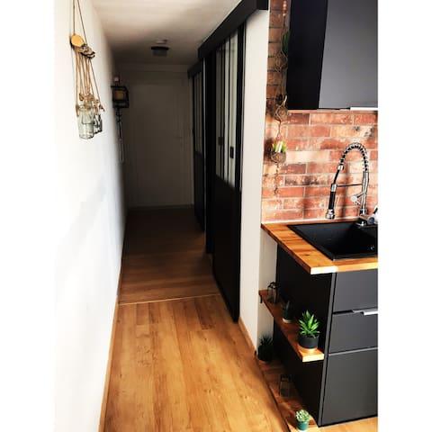Le couloir distribue l'entrée ainsi que la petite chambre et la salle de bain avec deux verrières coulissantes.