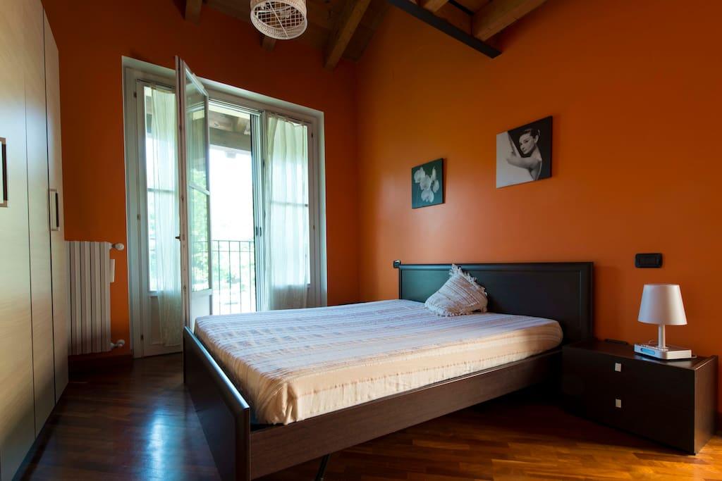 Romantica camera da letto matrimoniale con tetto in legno sfalzato e palquet.