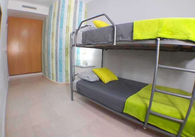 Bedroom 3, with bunk beds, window out onto the rear patio, fitted wardrobes and central aircon.