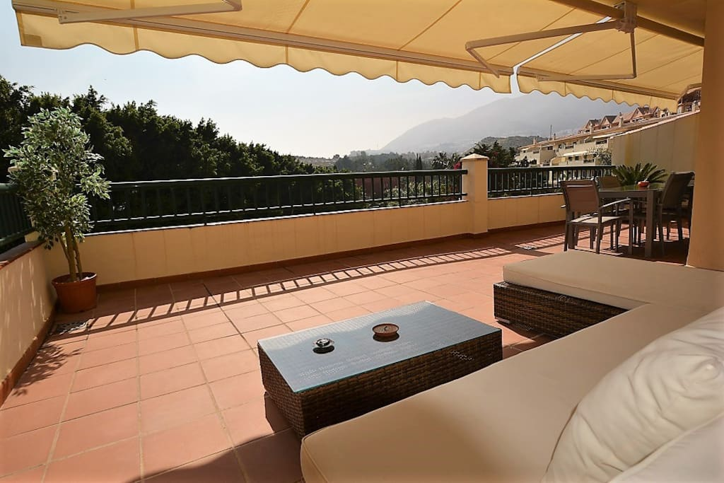 Spacious terrace with lounge sofa and dining table