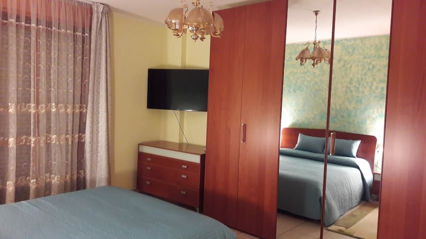 bedroom with a double bed and 55 inch tv
