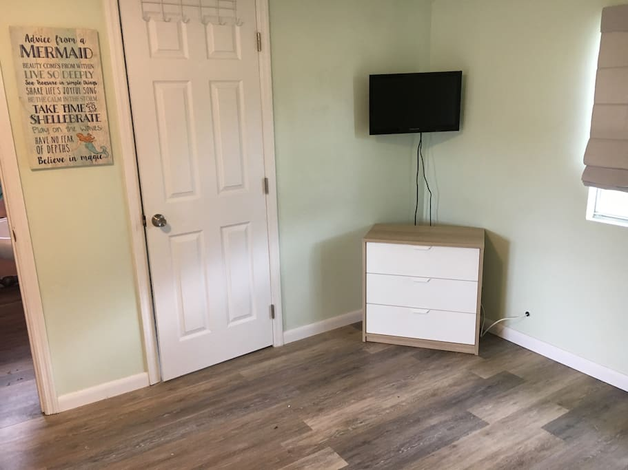 Cable TV with movie channels, laundry room and small dresser.