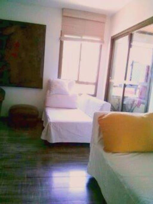 Living com 3 sofás, cadeiras, estante com Apple TV e DVD, Wi-Fi, abajures, ventilador de teto.