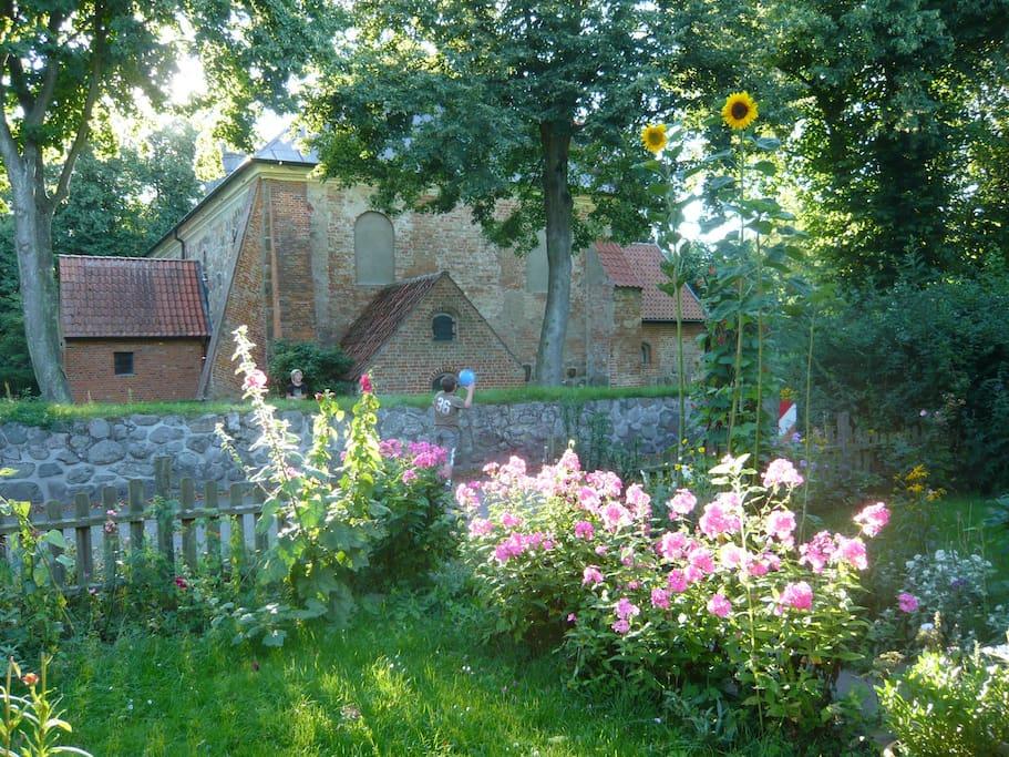 Vorgarten, im Hintergrund die Flemhuder Dorfkirche