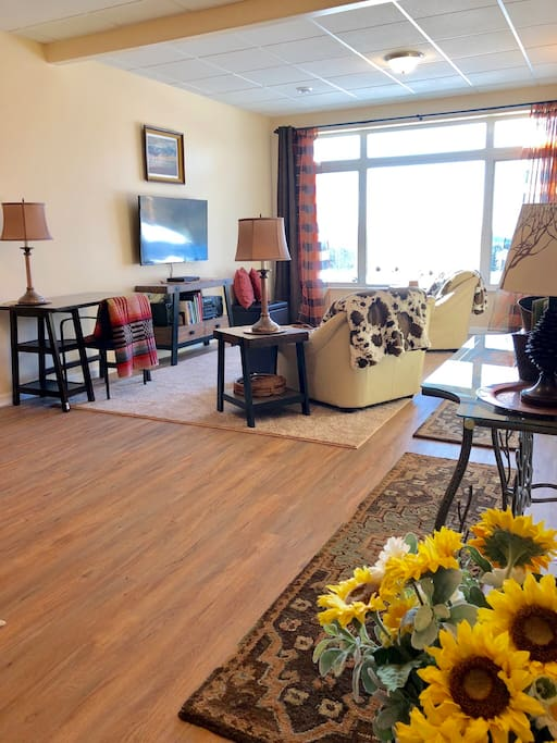 "View of the living room common area, is spacious and clean with cozy, relaxing ""Alaska cabin chic"" decor.  Our unit is barrier free providing easy wheelchair access and it has 3.0 wide doors."