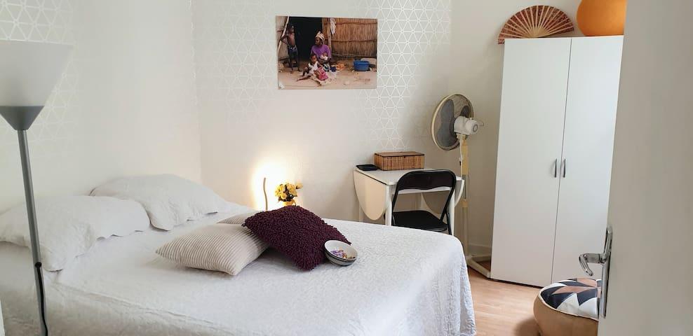 Vue d'ensemble de la chambre. Petite table - bureau avec chaise. Armoire avec penderie et complément de linge de toilettes et draps.