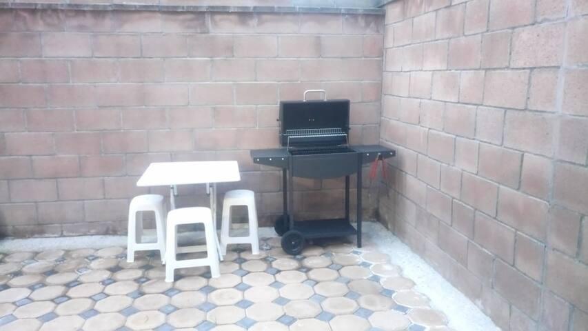 Parrilla en patio trasero, mesa y bancos.