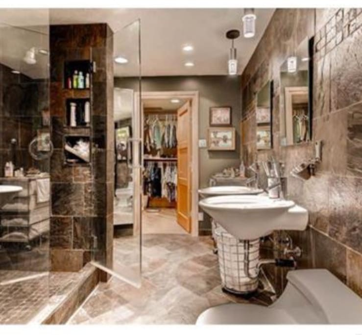 spectacular remodeled bathroom with dual shower heads and sinks and three view mirror