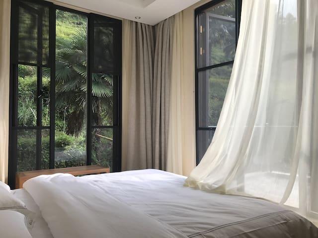 房间不大,榻榻米、落地窗,窗外便是山景与梯田。