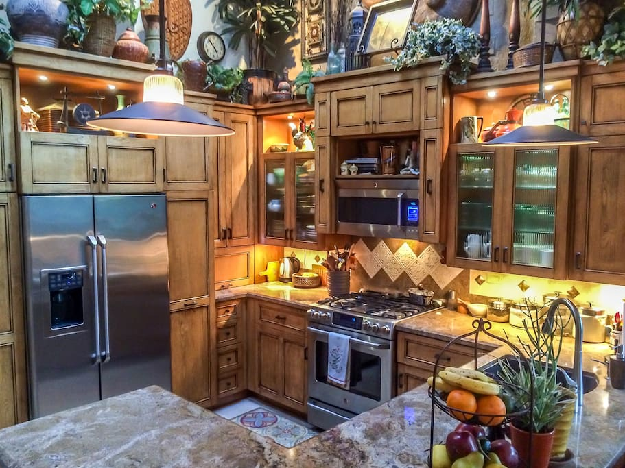 New custom chefs kitchen with stainless steel appliances, granite counter tops, skylights, vaulted ceiling, view to family with room and flat screen tv
