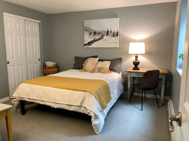 Bedroom with queen bed, desk and chair, double closets