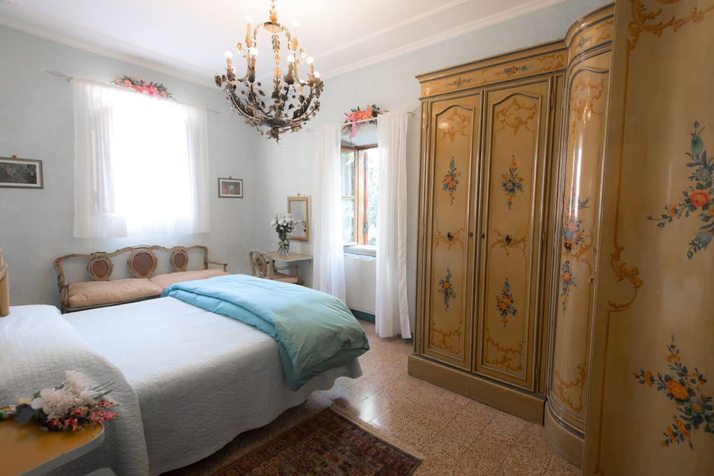 A bedroom with Queen Bed and hand painted antique armoire