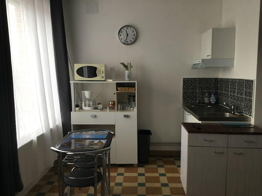 Coin cuisine avec la vaisselle, micro-onde, cafetière  (café,  sucre), réfrigérateur, plaques de cuisson