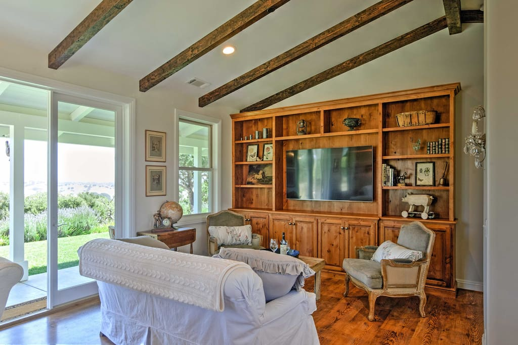 Wood beams, stunning views, and French country style decor adorn the interior.