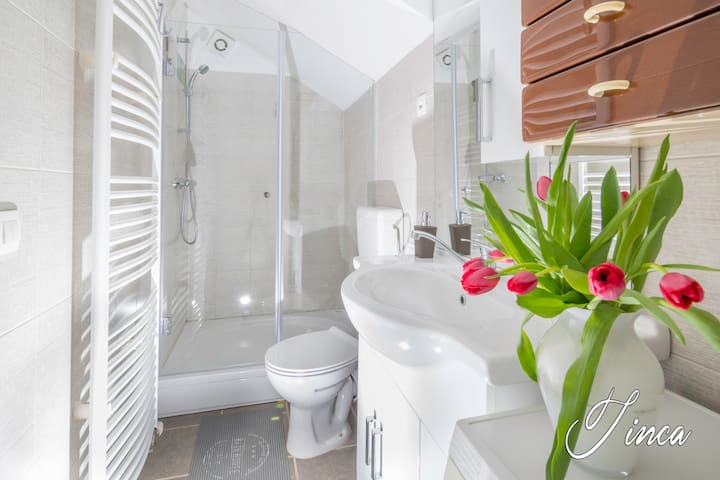 Beautiful bathroom with shower, toillet, washing machine, towels , shover gel, hair dryer