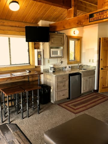 Dining table and kitchenette and mounted TV with satellite