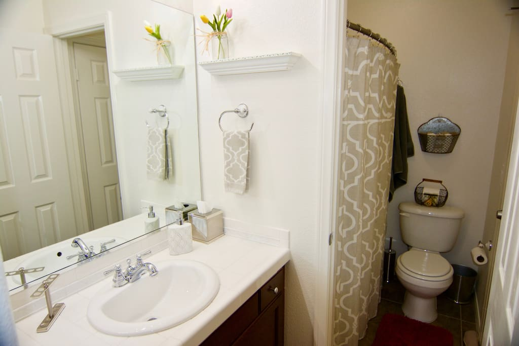 Full bath, with shower, tub and commode in separate space from sink and mirrors.