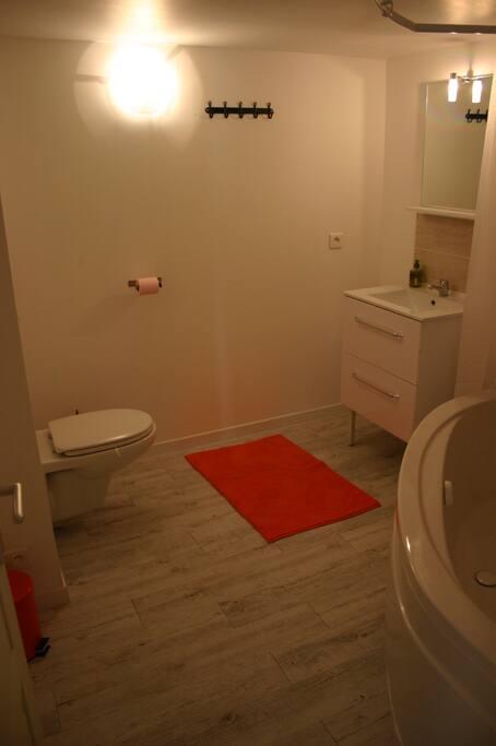Salle de bain fermée avec WC suspendu, baignoire d'angle et sèche-serviette
