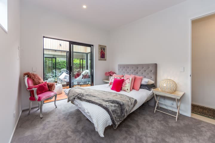 The lovely master bedroom with built in wardrobe and ensuite offers access through the double glazed sliders to a private, sunny and sheltered deck. This gorgeous room is complimented by velvet thermal backed curtains and cedar shutters.