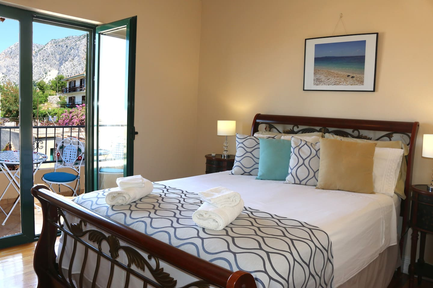 Bedroom with queen sized bed and small balcony