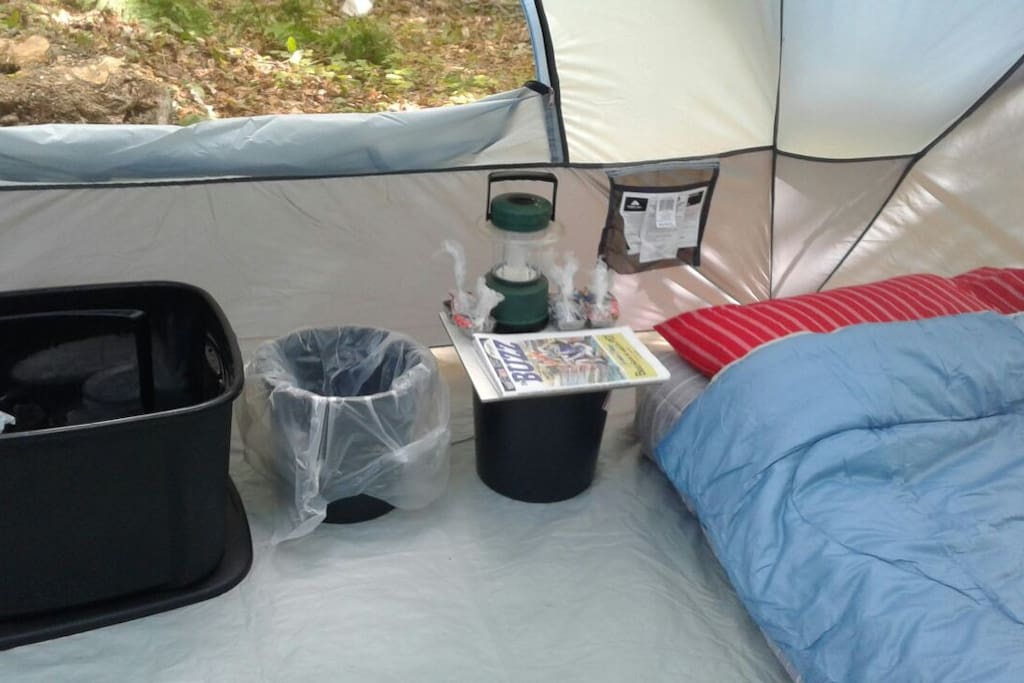inside rental tent with full air mattresses, lantern, side table, box of amenities, ect