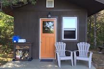 Front of cabin with washstand, water basin and wood stack.