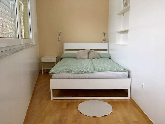 A private bedroom overlooking a  garden, with queen size bed