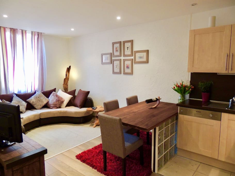Open plan living space with fully equipped kitchen, eating area and sofa