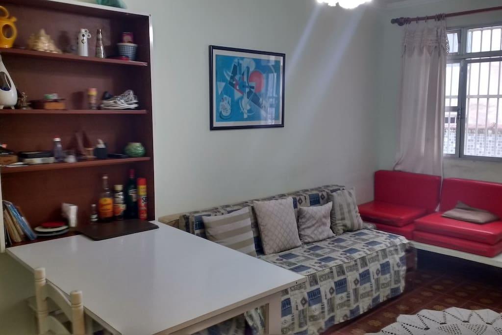 Sala com mesa ,sofa cama, TV e ventilador de teto