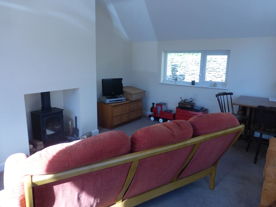 The living area and dining space with wood stove burner.