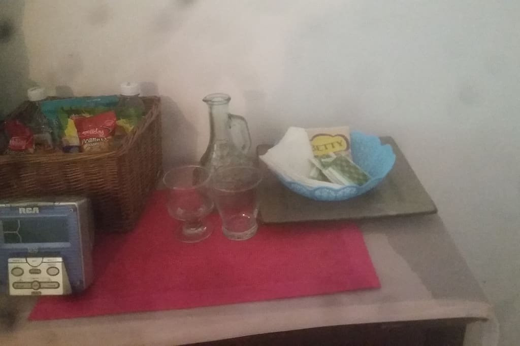 new snack table with snack basket with peanuts chips cracker bottled water tea creamer glasses with water glass and radio and drawers for some more clothes